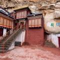 Thakthok klooster is tegen een rots gebouwd rondom een oude meditatiegrot